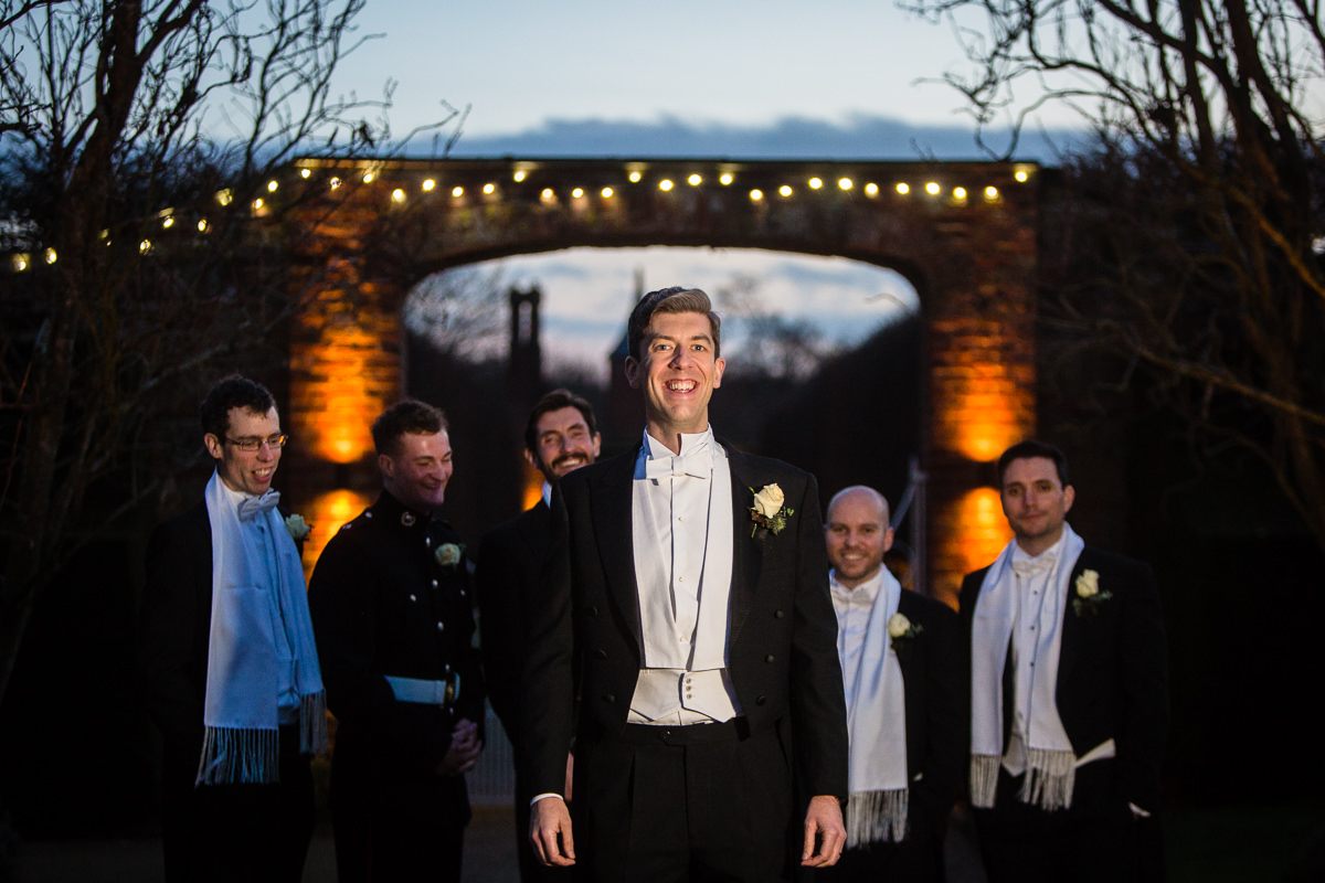 groom in twilightlooking really happy with the groomsmen in the background at combermere abbey outside the pavillion