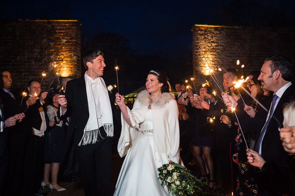 bride and groom looking really happy as they go through sparkler tunnel at combermere abbey, whitchurch shropshire. charlotte giddings photography recommended photographer
