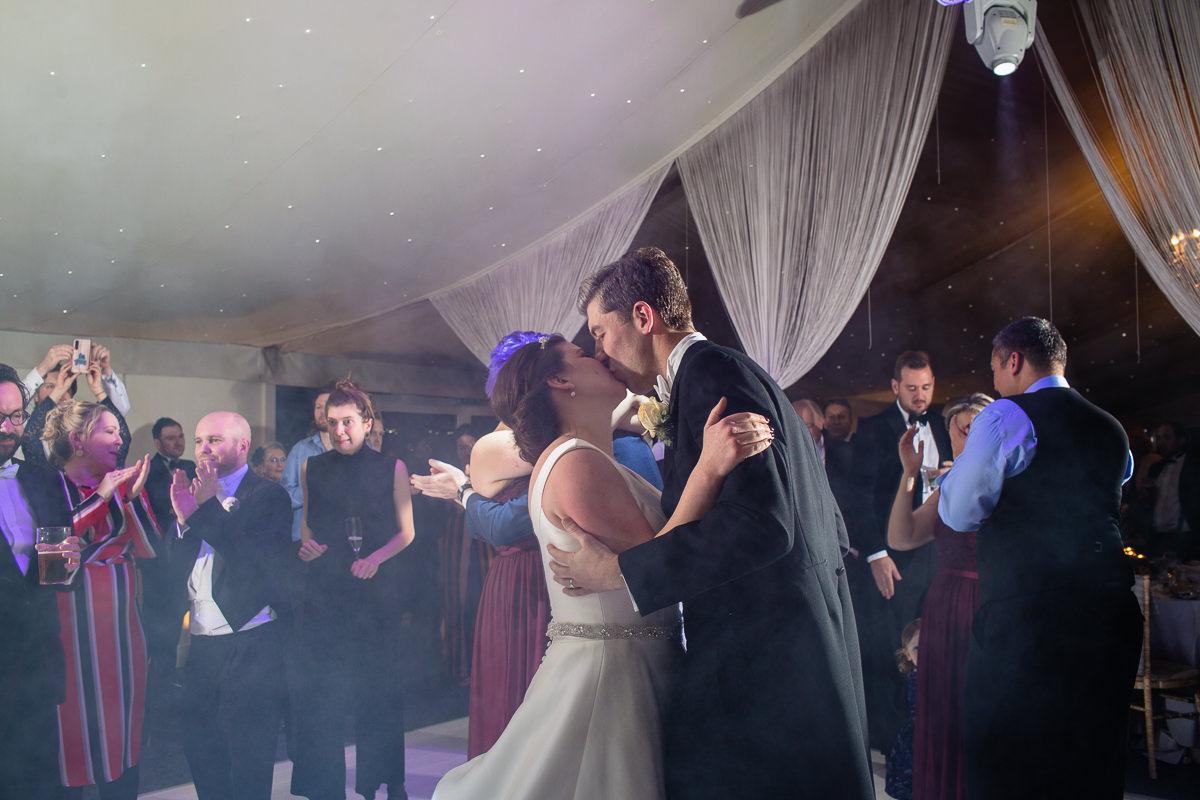 bride and groom kissing at the end of their first dance on the dance floor in the pavillion, combermere abbey