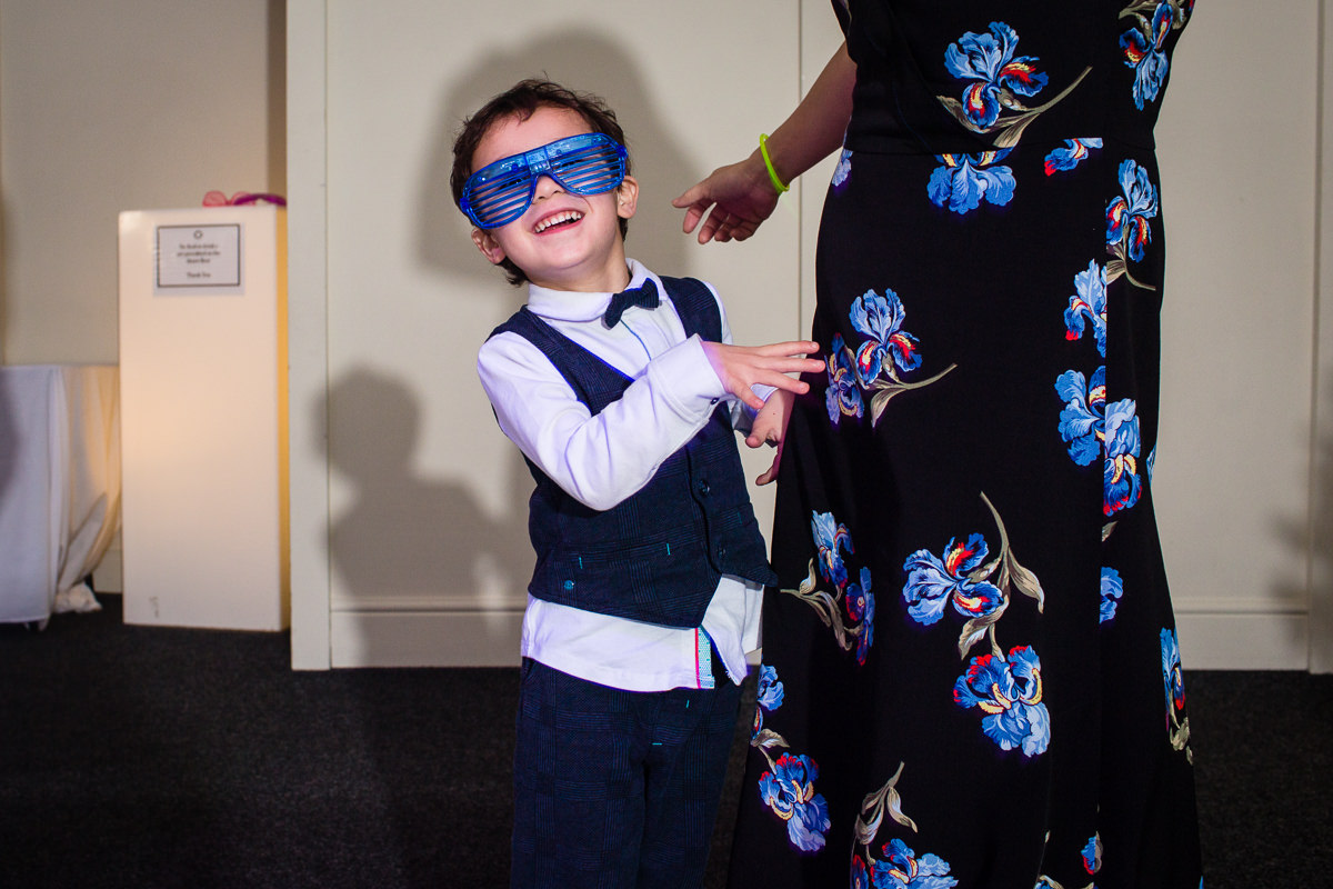 little boy in glow in the dark fancy dress glasses dancing to the dance floor at combermere abbey, shropshire wedding venue