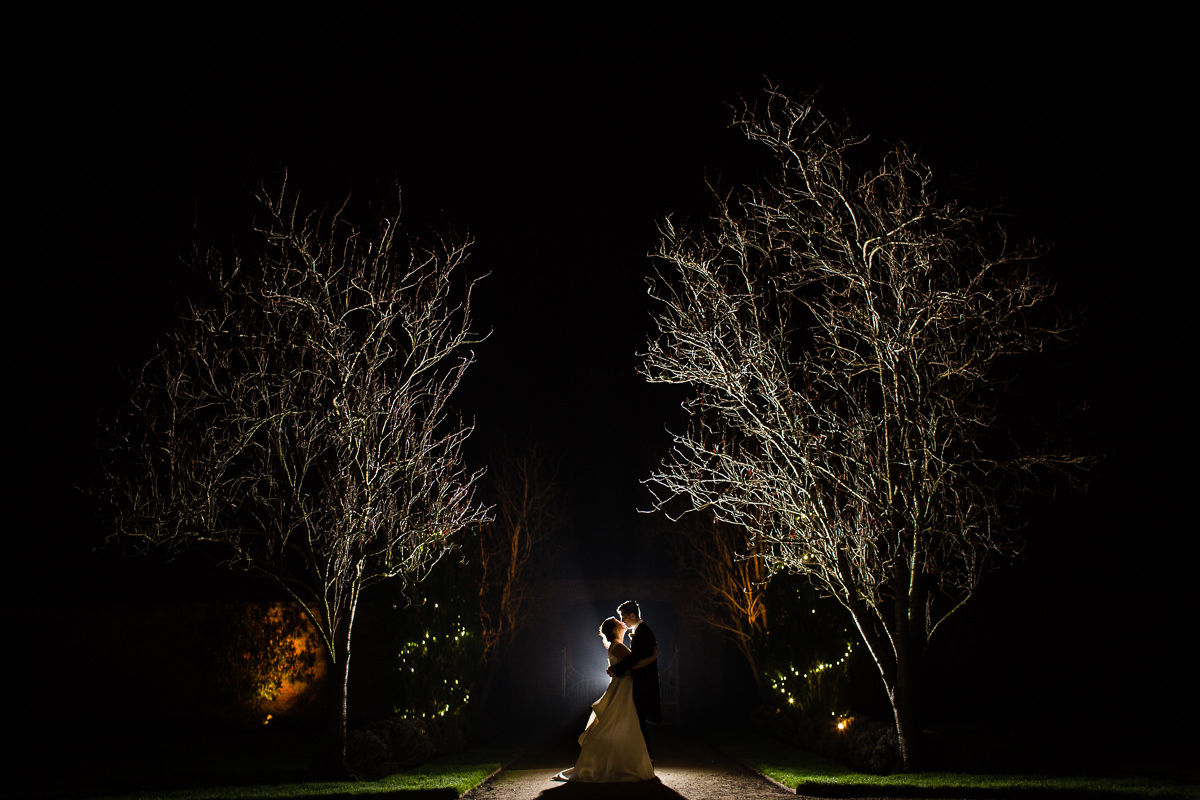 statement photo of bride and groom kissing as they stand in the grounds at night time at combermere abbey