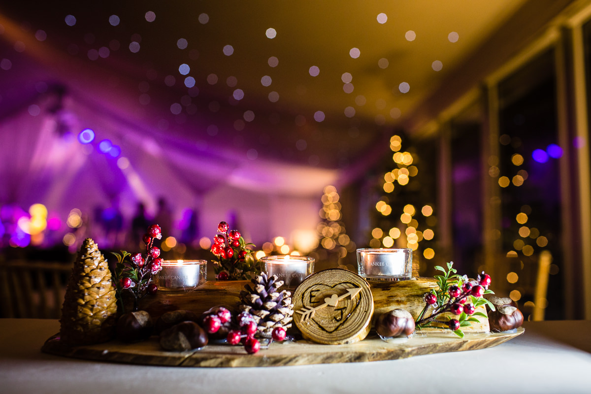 winter display of pine cones, candles, bark and mistletoe in the pavillion, combermere abbey with lots of bokeh, charlotte giddings photography