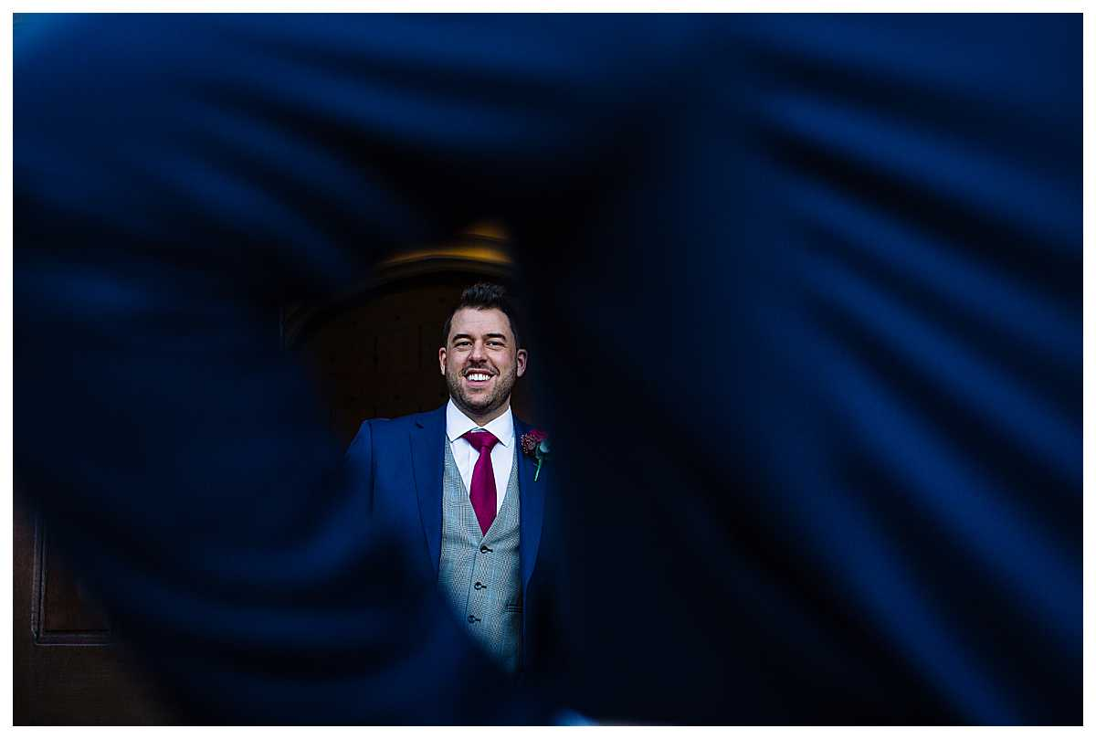 shot of groom wearing navy suit and red tie looking happy on his wedding day at tyn dwr hall