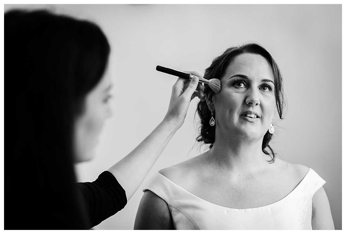 makeup artist applying finishing touches on brides makeup at tyn dwr hall wedding