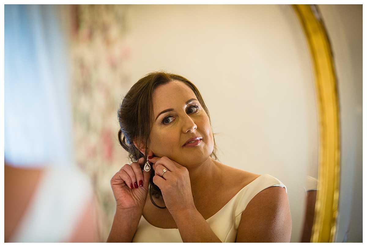 bride putting beautiful teardrop earrings in before leaving to get married at tyn dwr hall