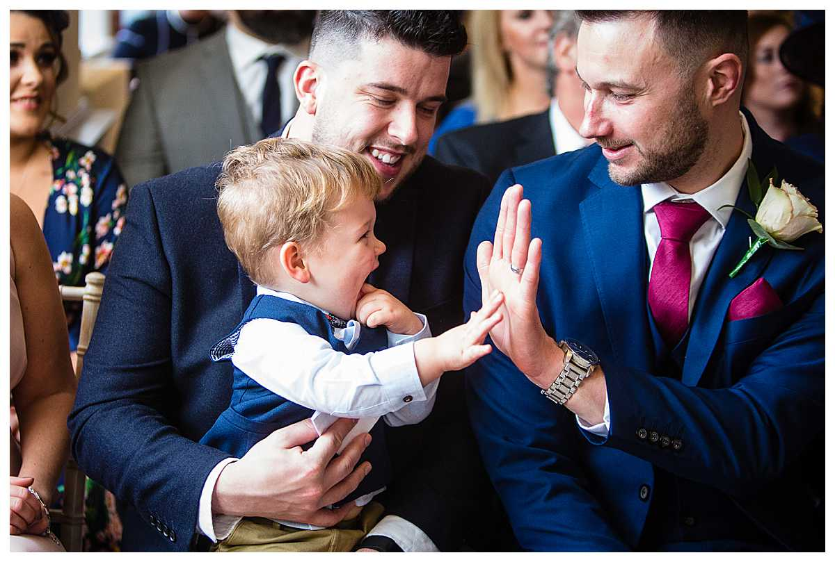 young page boy high five the groomsmen at wedding at tyn dwr hall, llangollen