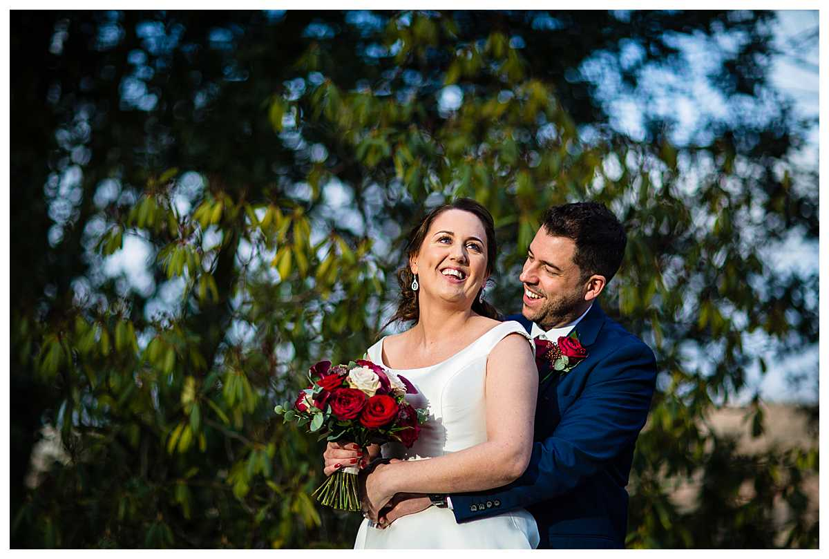 bride and groom in beautiful golden light giggling at tyn dwr hall in the grounds