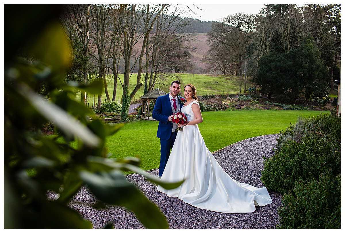 posed bride and groom in the gardens of llangollen wedding venue tyn dwr hall