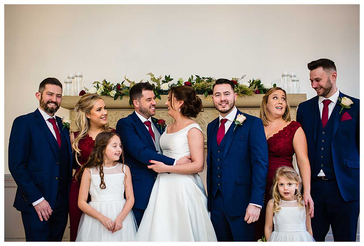 bridal party in the ceremony room at tyn dwr hall in red bridesmaid dresses and navy suits
