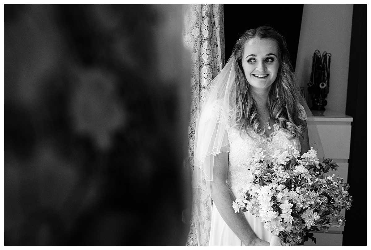 Bride looking out of the window excited to see wedding car pulling up, whitchurch shropshire wedding photographer
