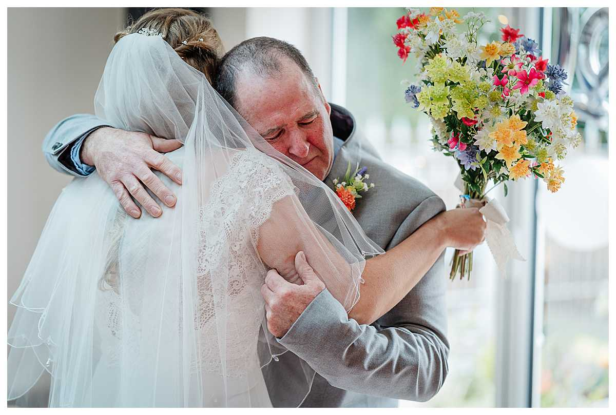 father of the bride emotional and giving his daughter a huge cuddle when he sees her ready in her wedding dress, wedding photographer shropshire