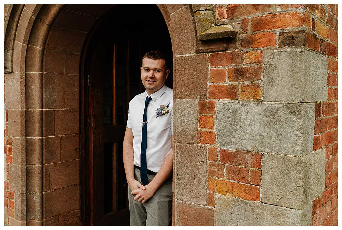 groom looking happy and relaxed in the doorway at marbury church wedding shropshire