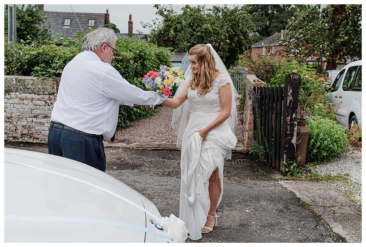 driver handing bride her bouquet as she gets out the car at marbury church shropshire