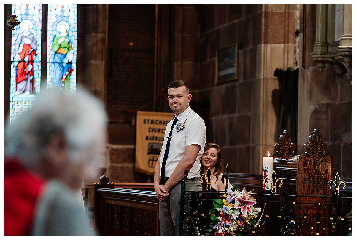 groom watching his bride, smiling, as she walks down the aisle at marbury church shropshire