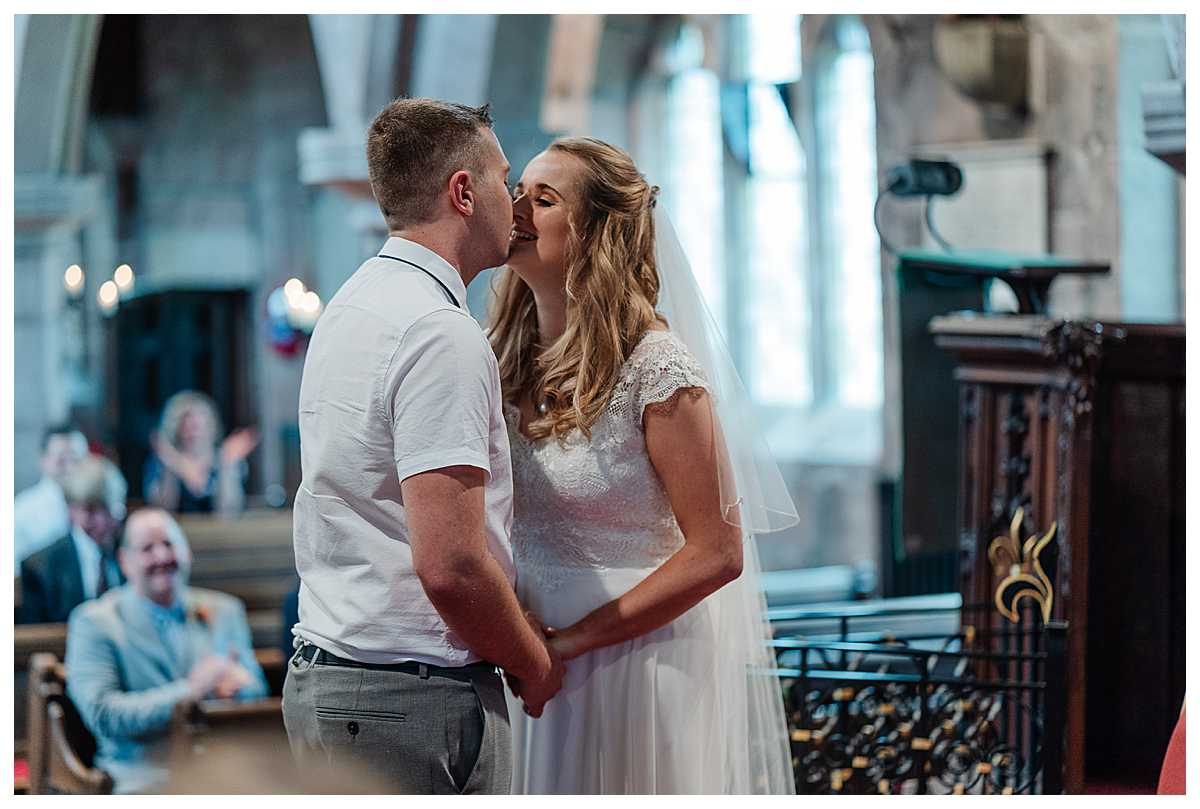 bride and groom first kiss as husband and wife, top of the aisle, marbury church, whitchurch, shropshire