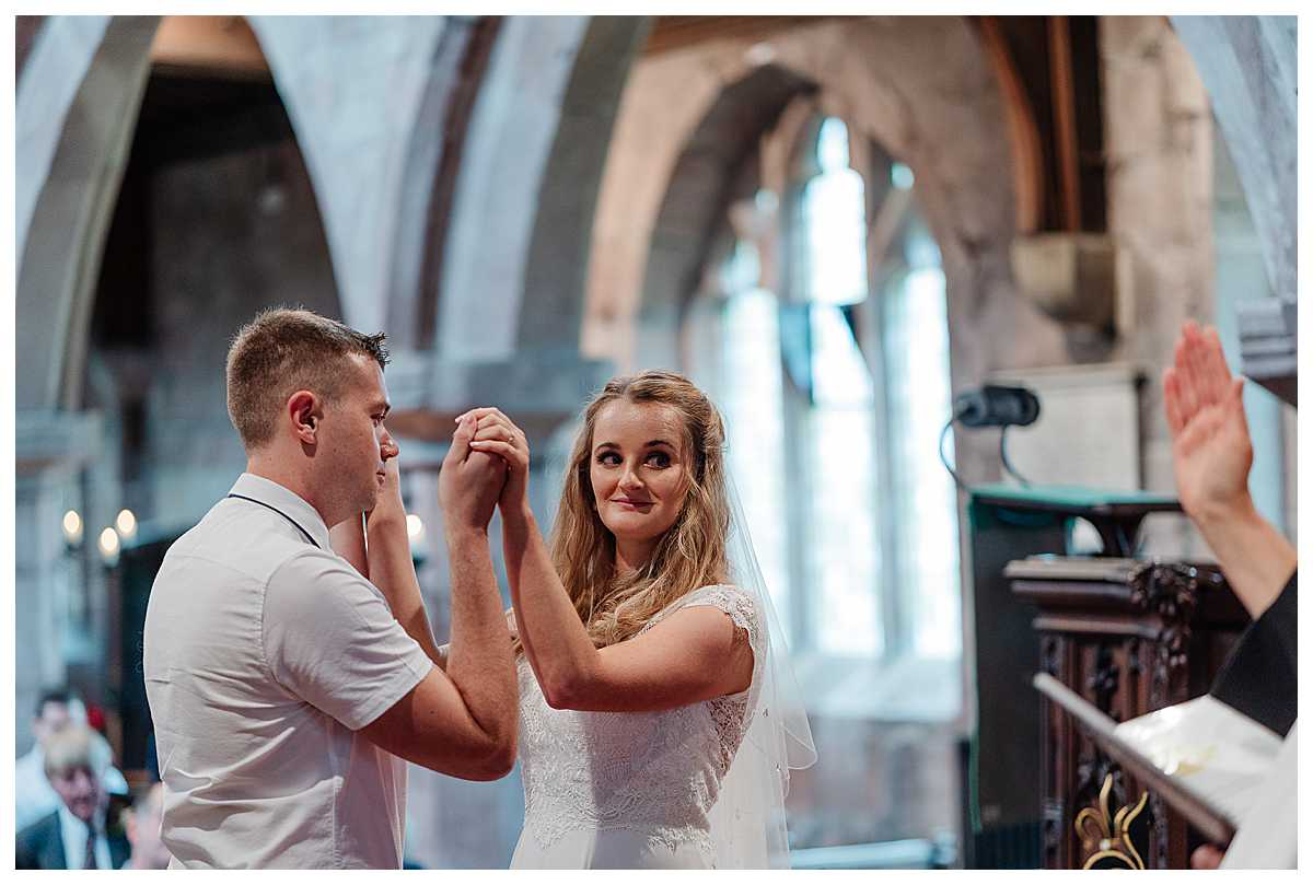 bride and groom holding hands as vicar conducts wedding blessing - shropshire wedding photography