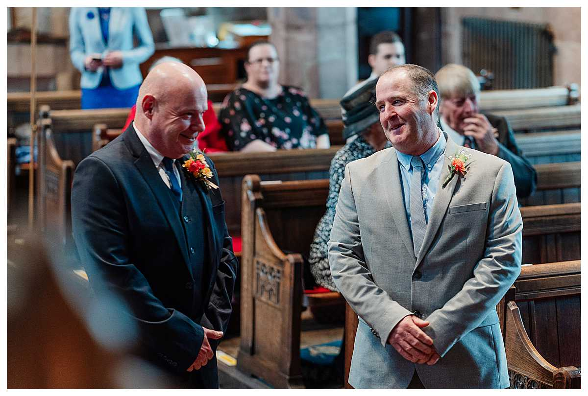 father of the bride and father of the groom exchanging banter as the bride and groom sign the register
