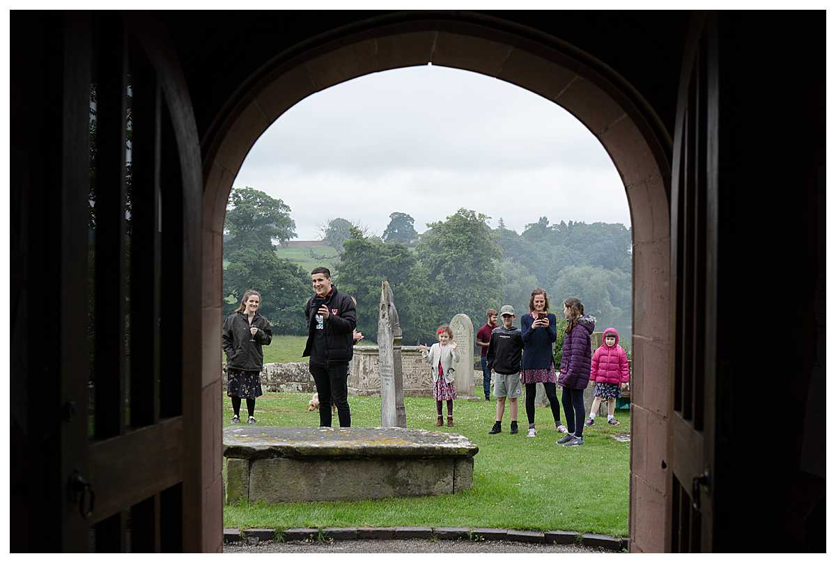 extended family watching the bride and groom walking out of church - excited to see them, shropshire wedding photographer