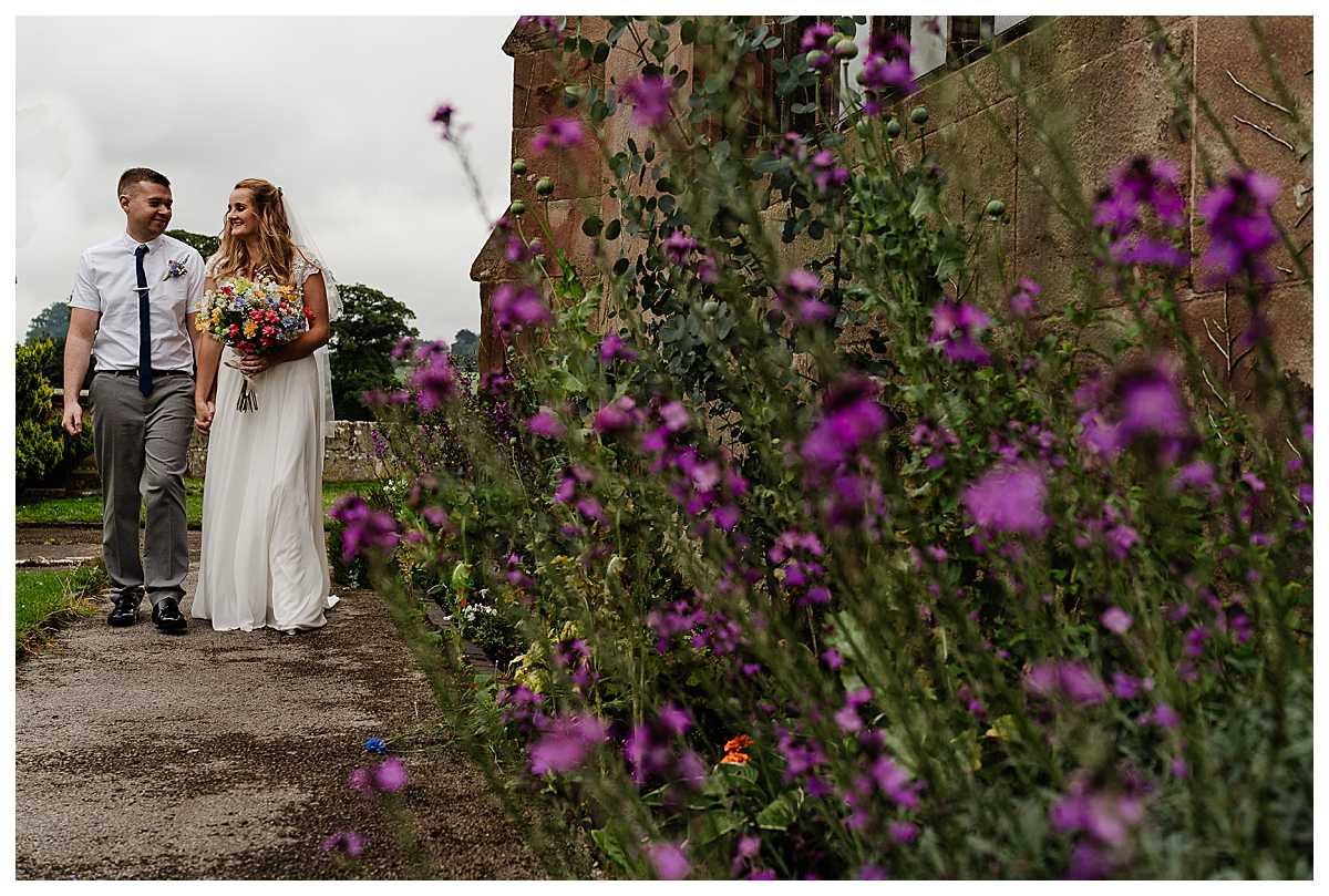 bride and groom walking around the outskirts of marbury church looking at one another, charlotte giddings photography