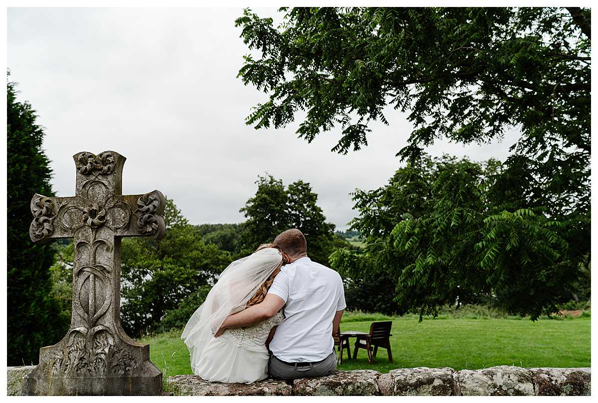 bride and groom sat on a wall at marbury church whitchurch shropshire - having a moment