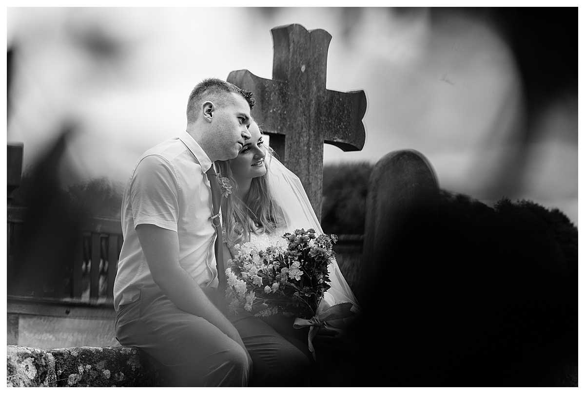 black and white photo of bride and groom cuddling while sat on a wall at marbury church whitchurch shropshire