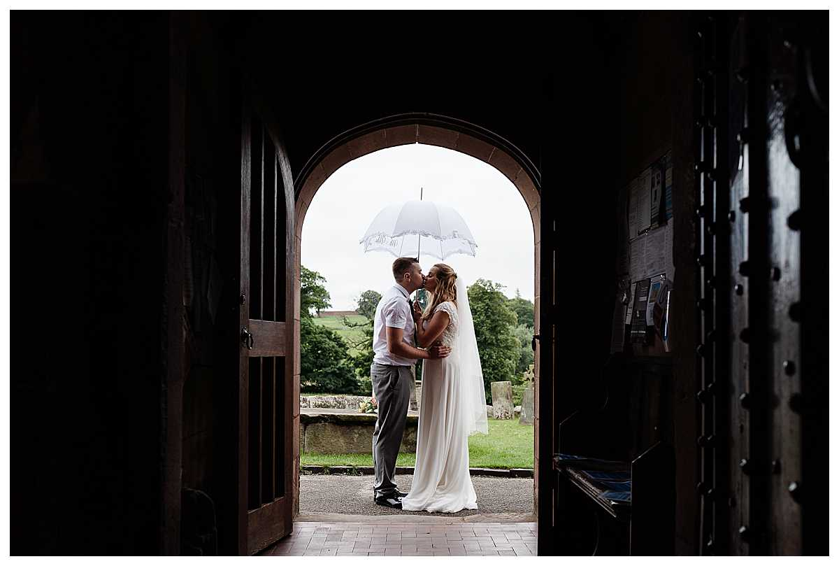 bride and groom kissing under an umbrella outside church at marbury, whitchurch, shropshire
