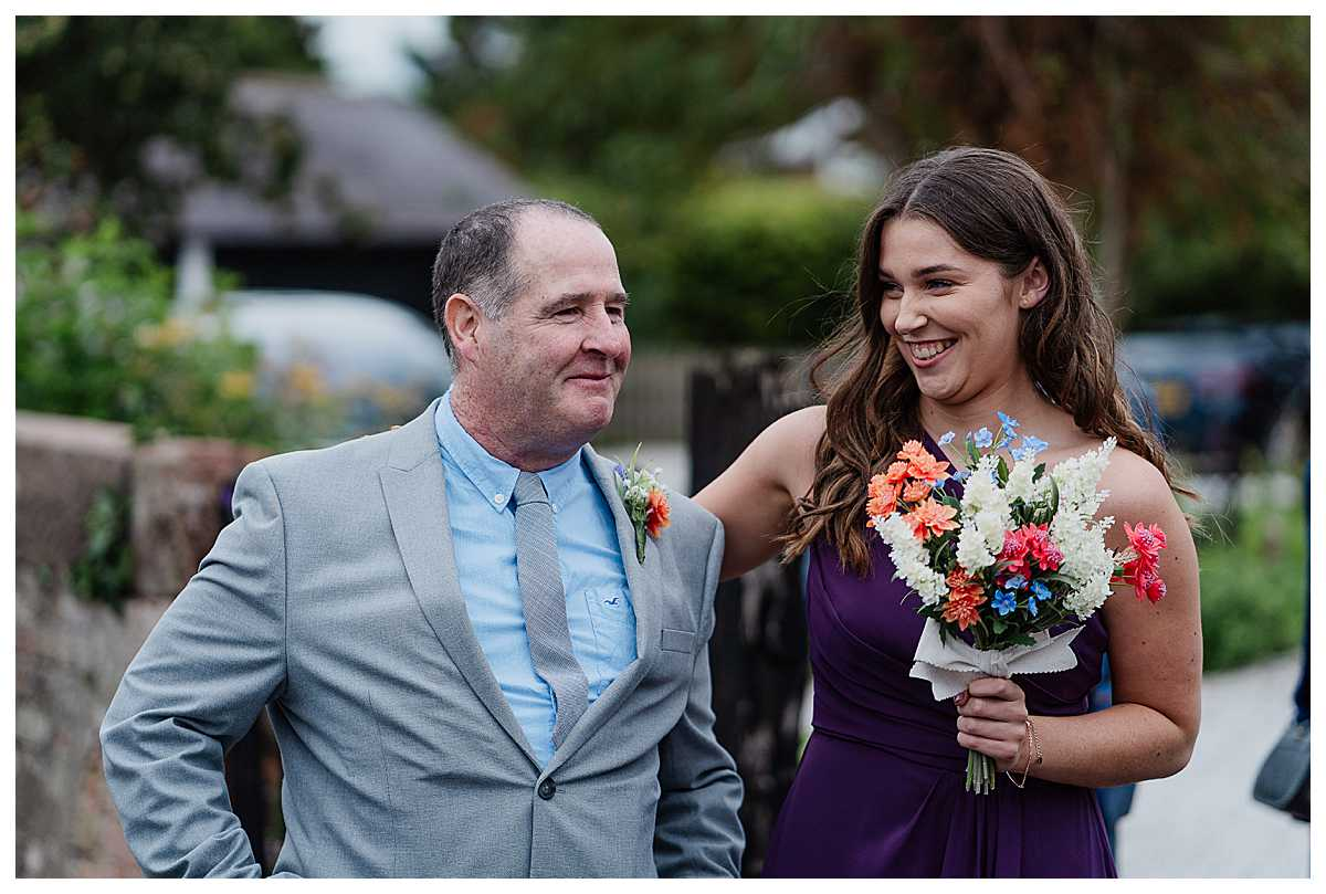 father of the bride emotional and very happy giggling with a bridesmaid outside the church, shropshire wedding photographer