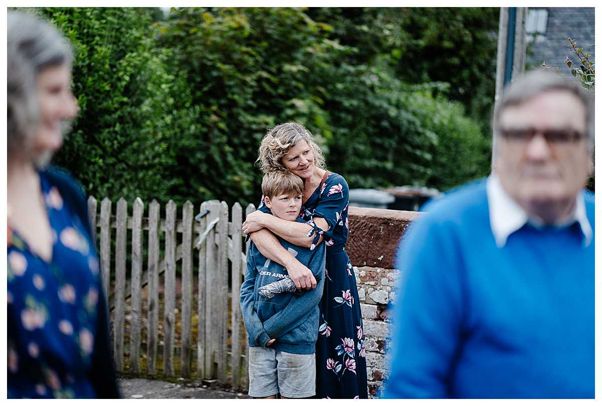wedding guest cuddling her son outside the church as she people watches - shropshire wedding photographer