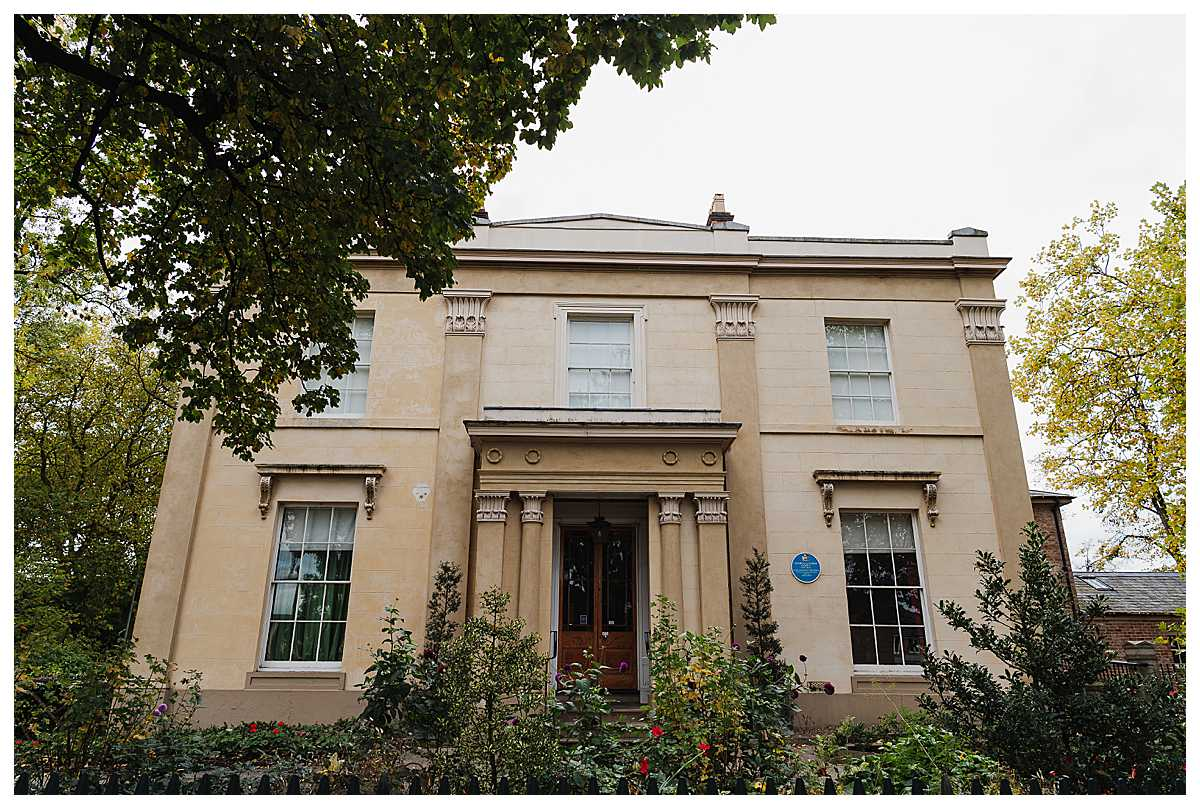 front of Elizabeth Gaskell's House on an autumnal day in october 2020 for a microwedding - charlotte giddings photography