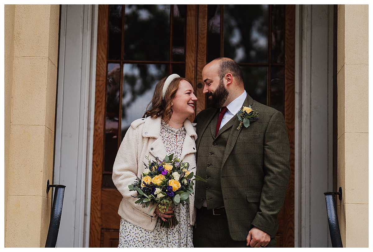 bride and groom looking into one anothers eyes in the doorway of elizabeth gaskells house, manchester wedding venue