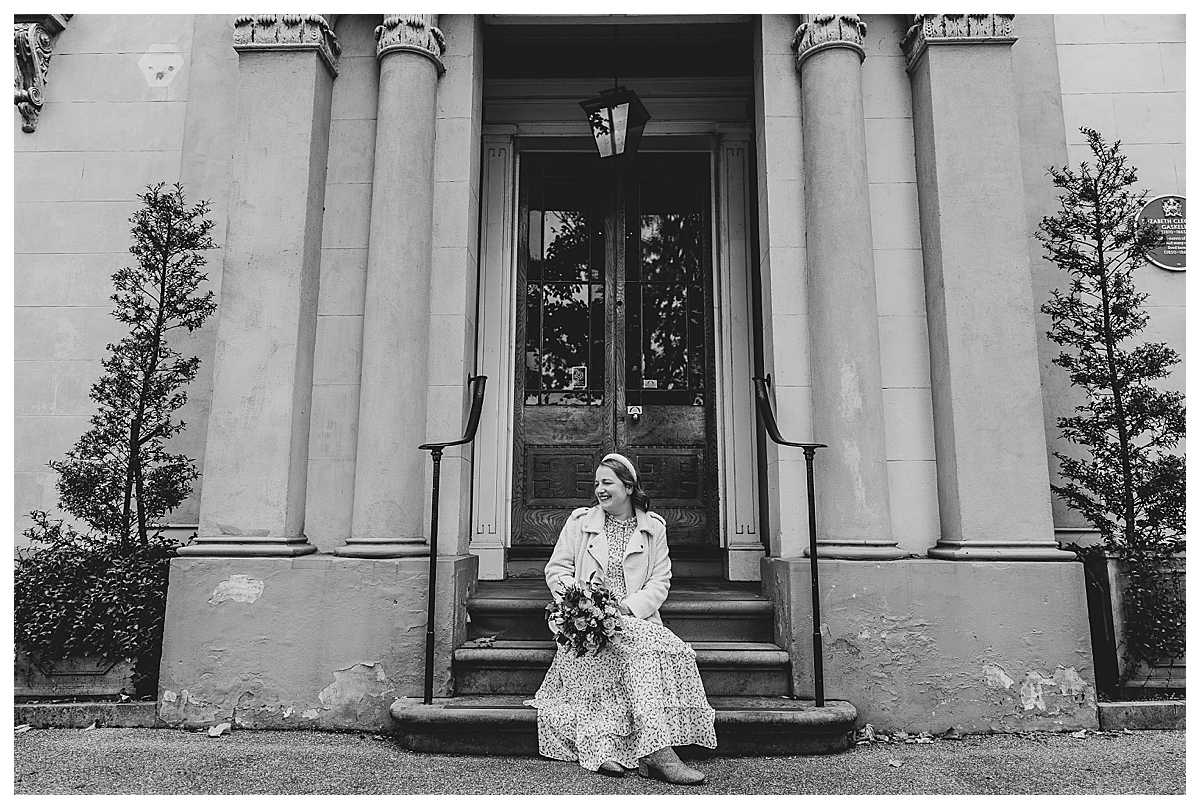bride sitting on the step of manchester wedding venue, elizabeth gaskells house looking incredibly happy