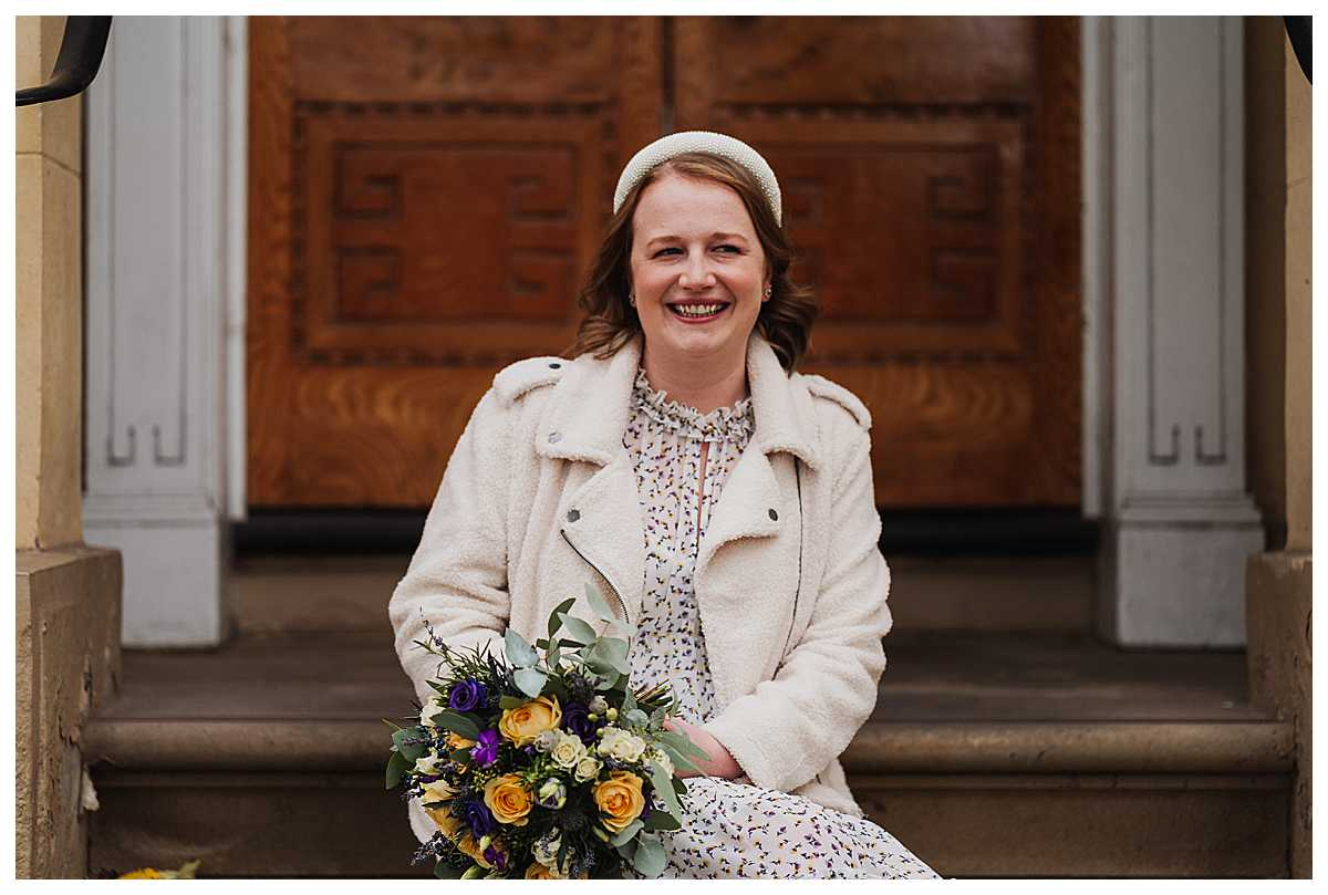 Emily the bride looking radiant looking cheekily at her husband to be in manchester on her wedding day
