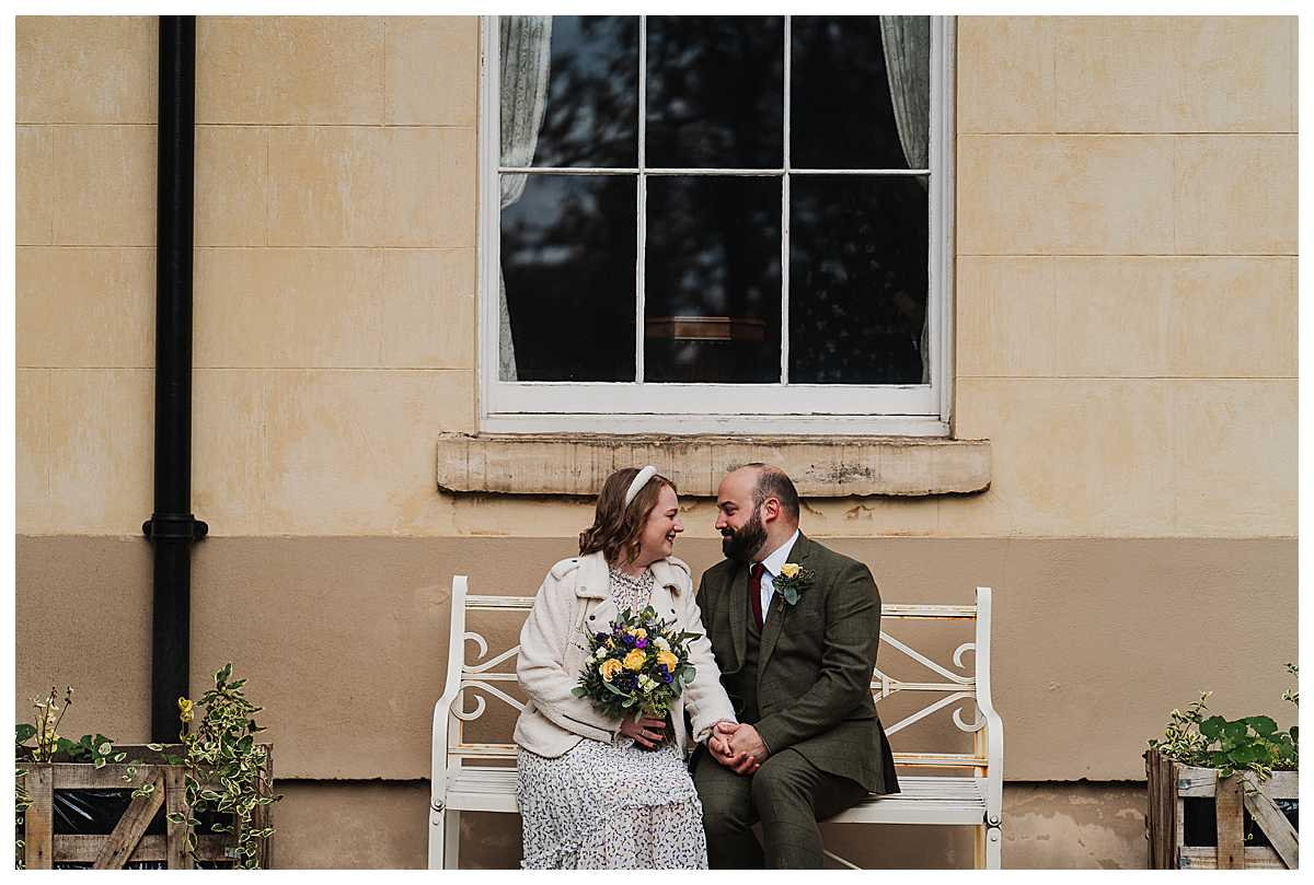 bride and groom sat on a bench in the garden of elizabeth gaskells house looking at one another lovingly - charlotte giddings photography