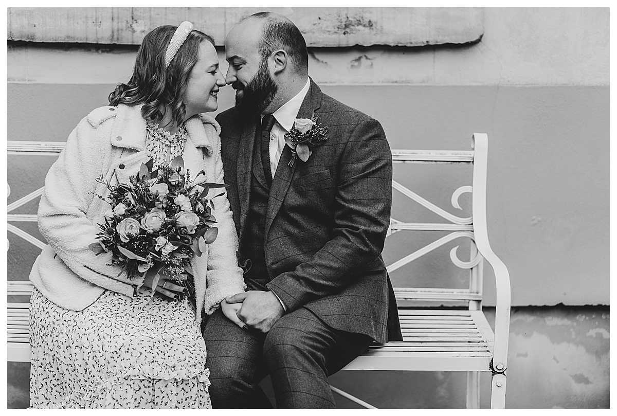 bride and groom doing eskimo kisses sat on a bench in the back garden of elizabeth gaskells house
