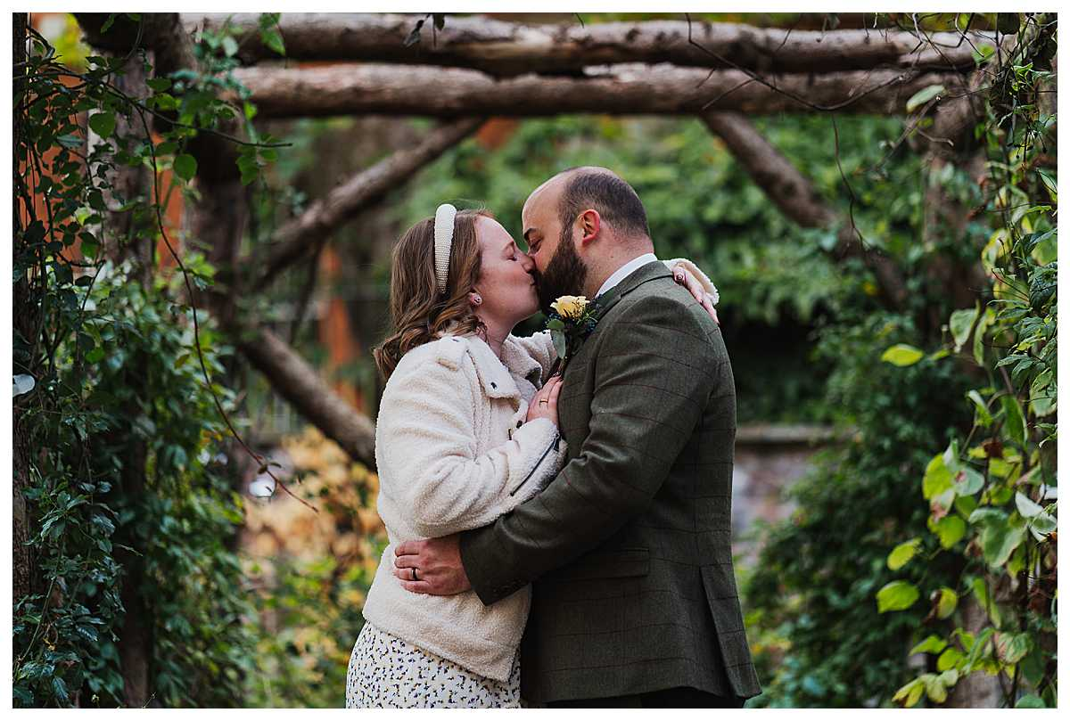 colourful photo of bride and groom having a kiss at elizabeth gaskell's house, manchester wedding photographer