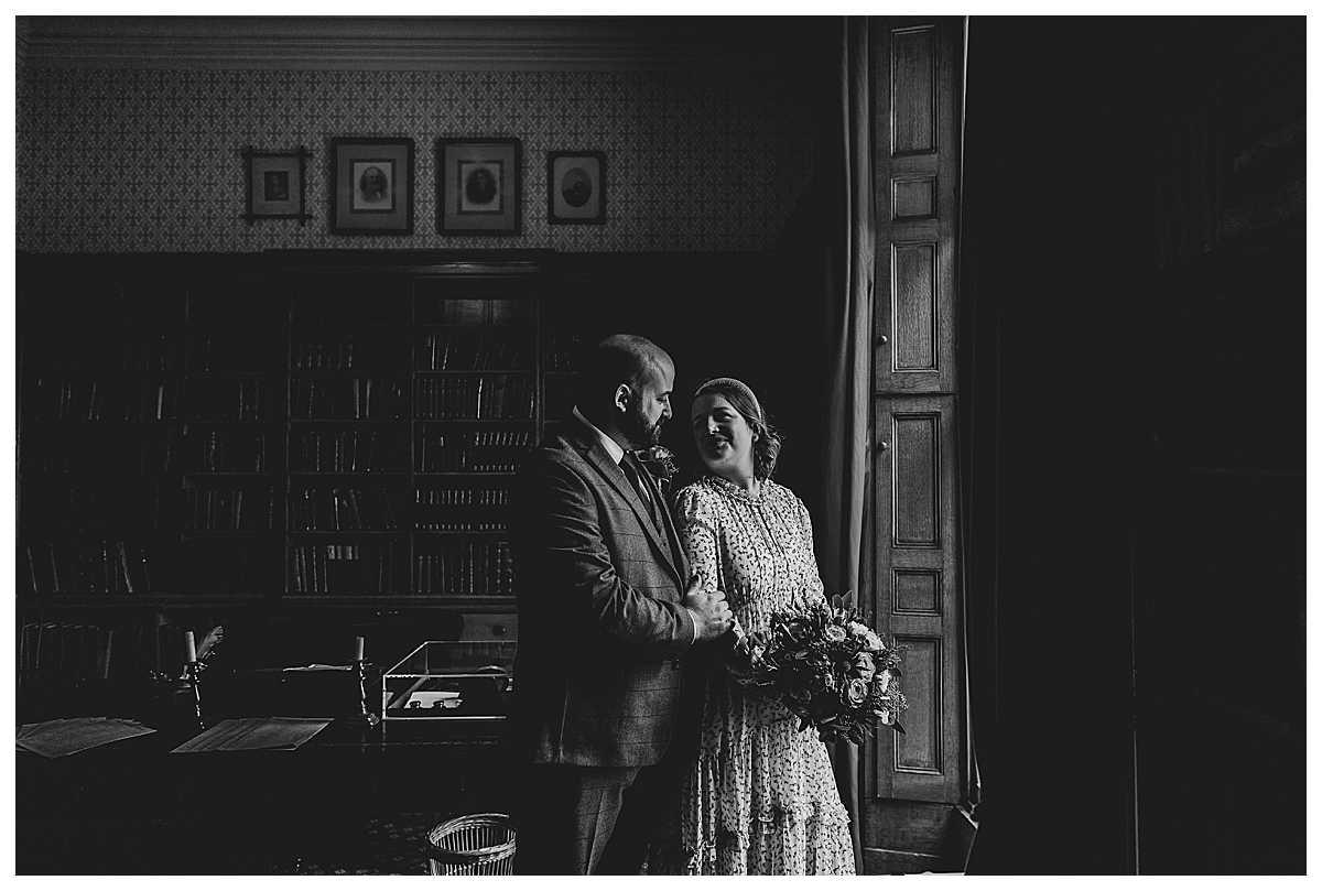 bride and groom cuddling in big bay window of the library in elizabethan house, elizabeth gaskells house
