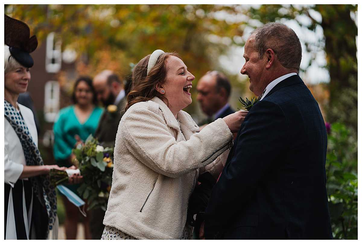 bride laughing hard with her dad as she does his button hole on his suite, manchester wedding photographer