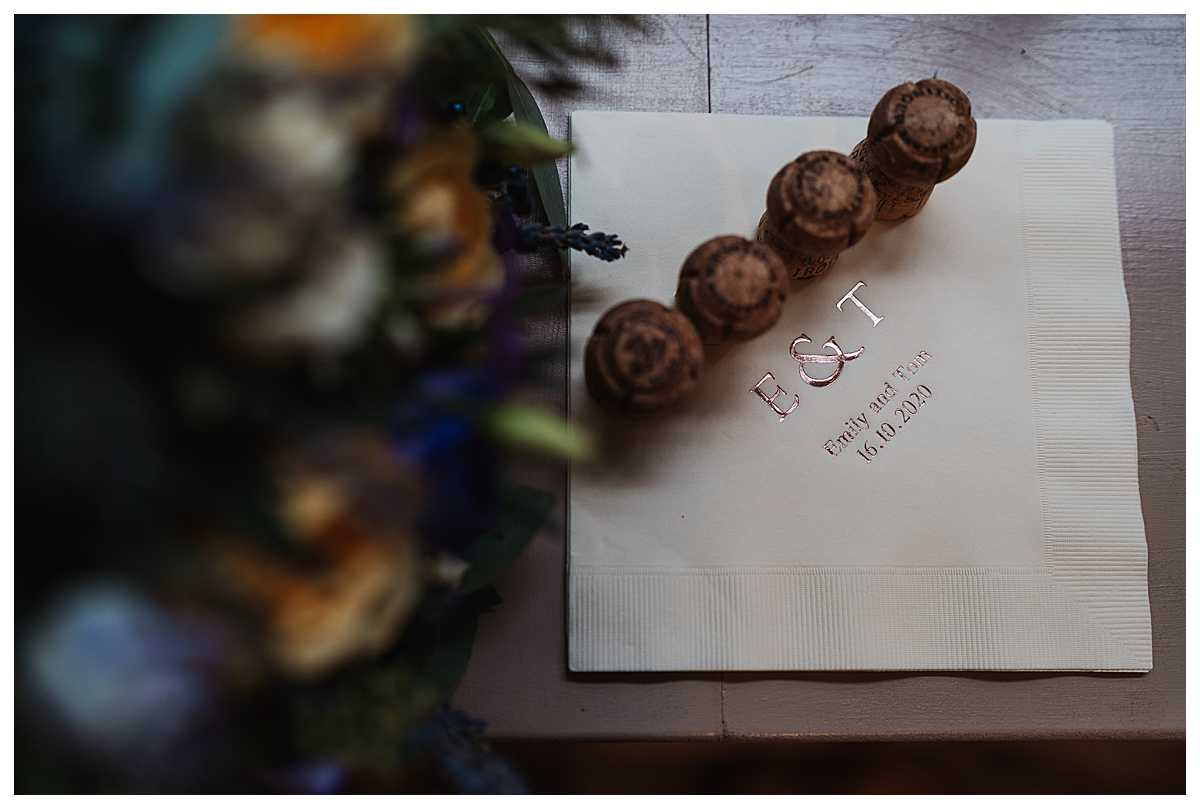 wedding details of perconalised napkins and champagne corks at elizabeth gaskells house