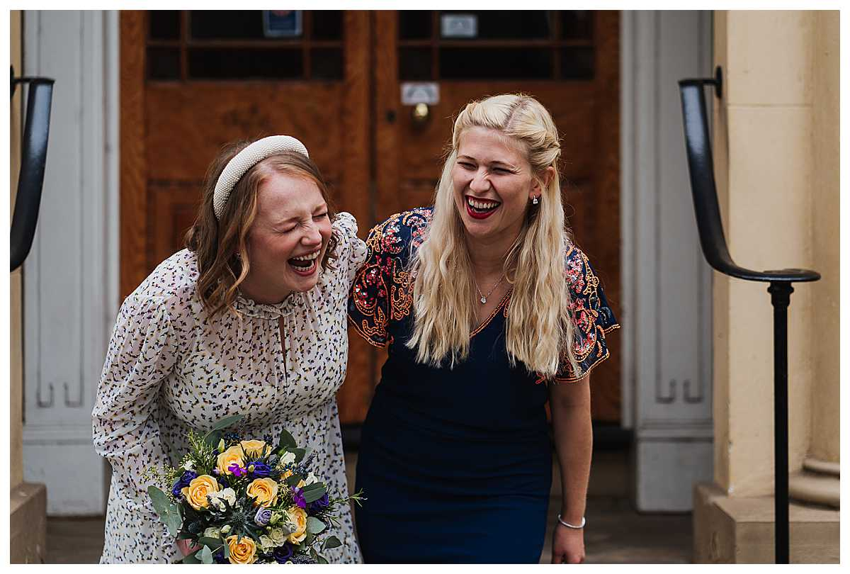 bride and best friend properly belly laughing outside manchester wedding venue, manchester wedding photographer