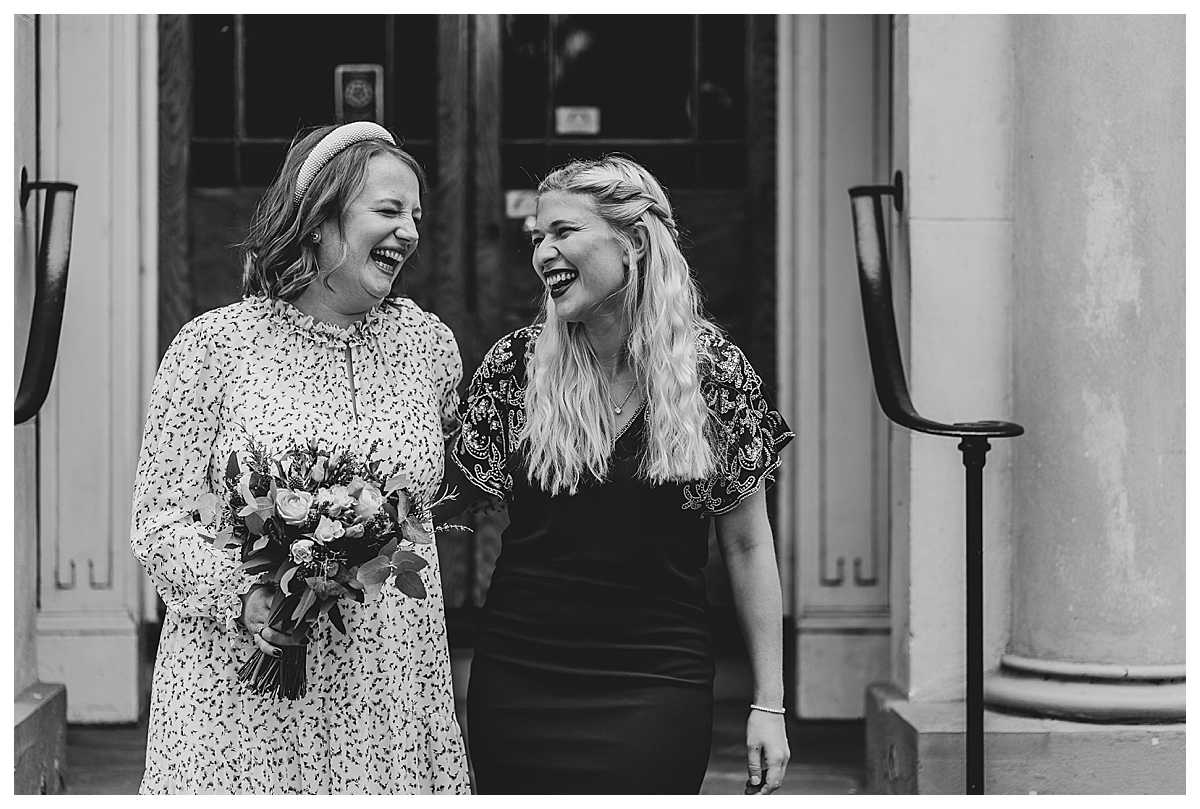 bride and her best friend having a ball and giggling together at microwedding in manchester