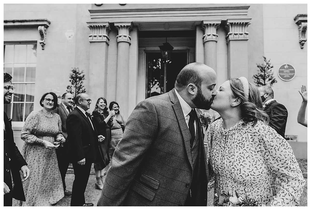 bride and groom kissing after having confetti thrown on them outside their wedding venue - charlotte giddings photography